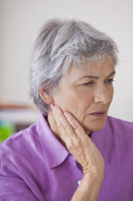 Older woman holding jaw in pain | Dentist Elgin IL