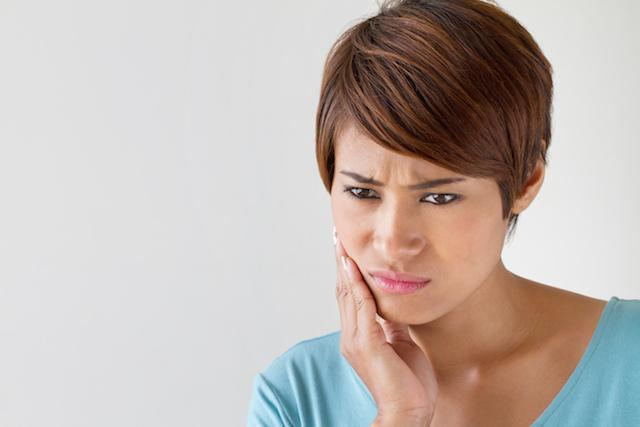 Woman holding jaw from pain | Dentist Elgin IL