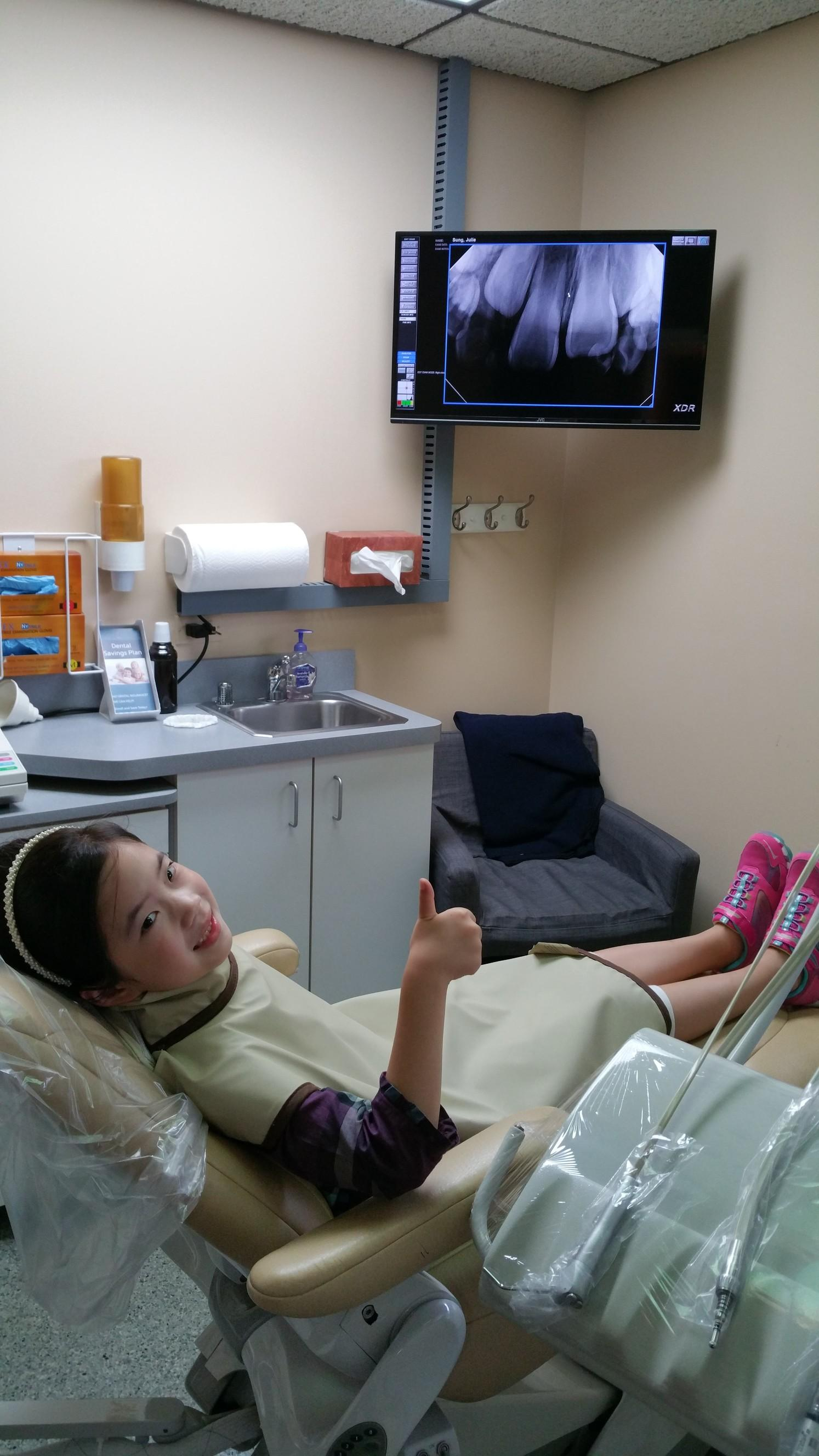 Small girl sitting in dental chair with dental x-ray on screen above chair | Elgin IL Dentist