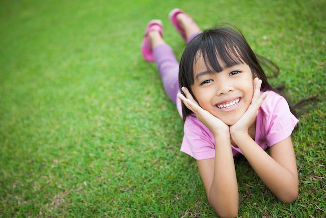 Girl Smiling while sitting on grass | Dentist Elgin IL